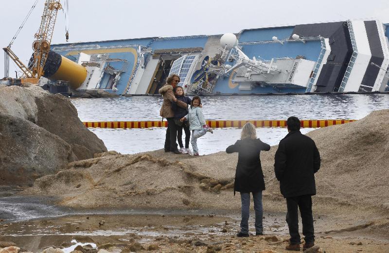"""turisti che si fanno foto """"ricordo"""" con la Costa Concordia sullo sfondo, all'Isola del Giglio"""