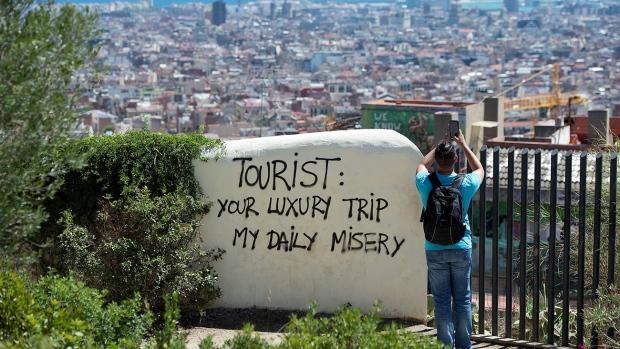 Turisti e frasi di protesta contro di loro a Park Guell a. Barcellona. (foto Josep LAGO / AFP)